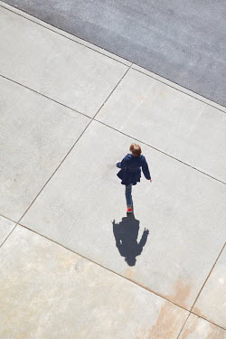 Susan Fox WOMAN WALKING ON SUNLIT CONCRETE Women