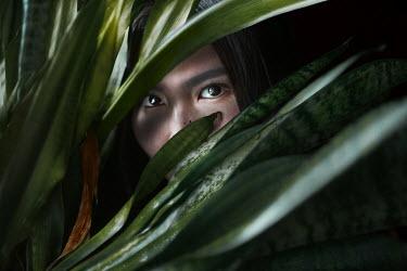 Kirill Sakryukin ASIAN WOMAN HIDING BEHIND PLANT Women