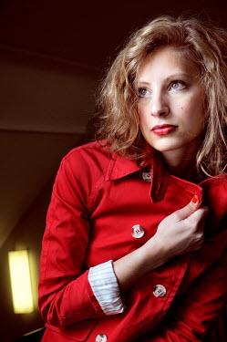 Ute Klaphake YOUNG WOMAN WEARING RED COAT IN PASSAGEWAY Women