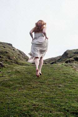 Clayton Bastiani YOUNG WOMAN RUNNING IN COUNTRYSIDE Women