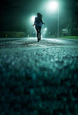 Stephen Mulcahey woman running down road at night time Women