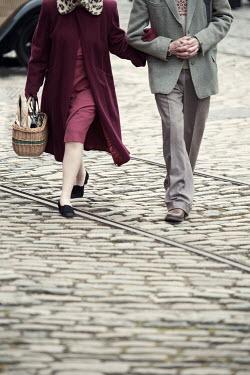 Lee Avison 1940s couple arm in arm walking on cobbles Couples