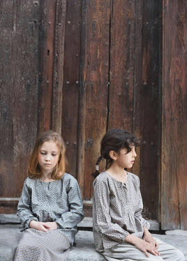 Tanya Gramatikova TWO LITTLE GIRLS SITTING BY WOODEN FENCE Children