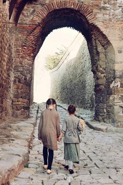 Tanya Gramatikova TWO LITTLE GIRLS WALKING ON COBBLED STREET Children