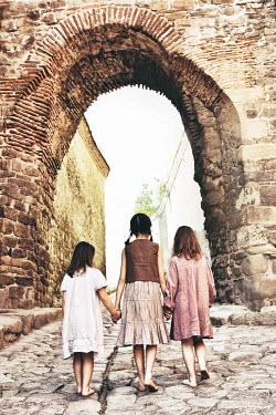 Tanya Gramatikova THREE LITTLE GIRLS WALKING ON COBBLED STREET Children