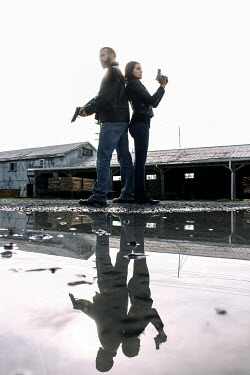 Stephen Carroll COUPLE WITH GUNS REFLECTED IN PUDDLE Couples