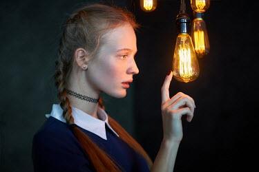 Alexander Vinogradov YOUNG WOMAN WITH PLAITS TOUCHING LIGHTBULB Women