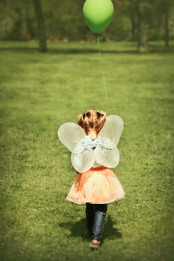 Buffy Cooper LITTLE GIRL WEARING FAIRY WINGS IN COUNTRYSIDE Children