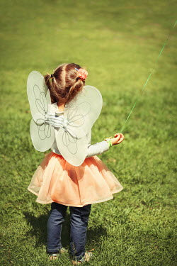Buffy Cooper LITTLE GIRL WEARING FAIRY WINGS IN FIELD Children