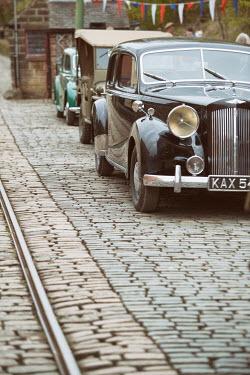 Lee Avison vintage cars parked on cobbled street Cars