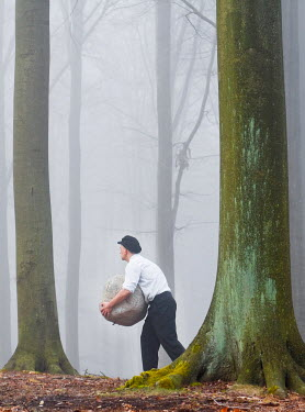 Leszek Paradowski MAN CARRYING LARGE ROCK IN FOREST Men