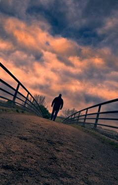 Tony Watson silhouette of man walking over a bridge. Men