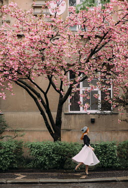 Marta Syrko RED HAIRED WOMAN ON STREET BY BLOSSOM TREE Women
