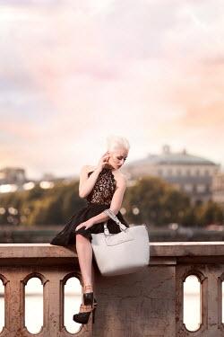 Dan Tidswell GLAMOROUS BLONDE WOMAN SITTING ON CITY WALL Women