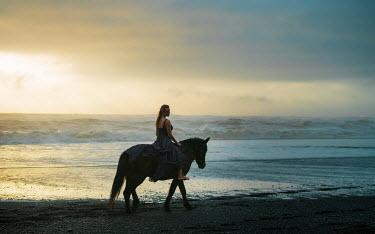 Dan Tidswell WOMAN RIDING HORSE ON BEACH AT SUNSET Women