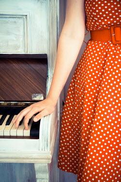 Elly De Vries WOMAN IN RED POLKA DOT DRESS BESIDE PIANO Women