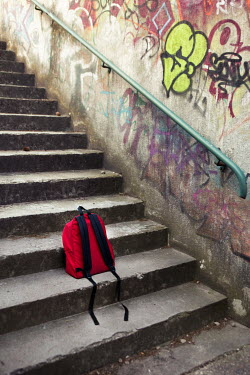 Kelly Sillaste RED BACKPACK LEFT ON URBAN GRAFFITIED STEPS Miscellaneous Objects