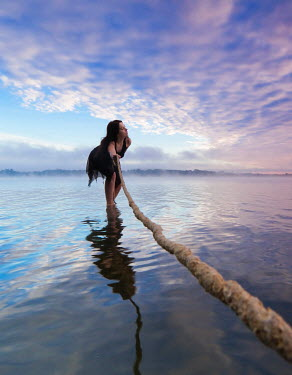 Leszek Paradowski BRUNETTE WOMAN PULLING ROPE IN MISTY LAKE Women