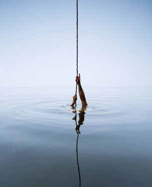 Leszek Paradowski MANS HANDS PULLING ON ROPE REFLECTED IN SEA Body Detail