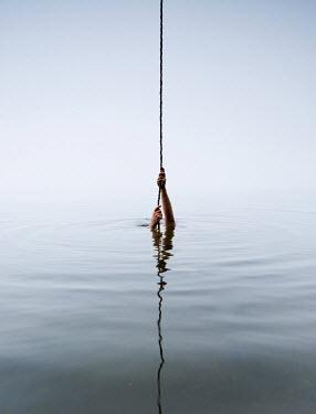 Leszek Paradowski MANS HANDS PULLING ON ROPE REFLECTED IN SEA Men
