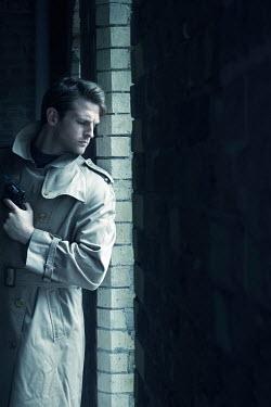 CollaborationJS man in a rain mac hiding in the shadows Men