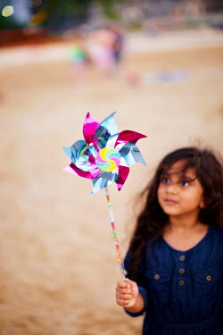 Robert Swiderski LITTLE GIRL WITH TOY WINDMILL ON BEACH Children