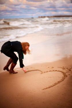 Robert Swiderski YOUNG WOMAN DRAWING HEART ON SANDY BEACH Women