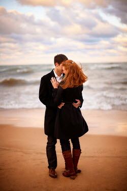 Robert Swiderski YOUNG COUPLE EMBRACING ON SANDY BEACH Couples