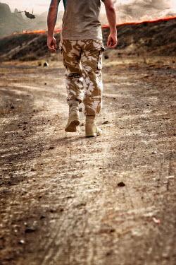 Nik Keevil SOLDIER WALKING ON DIRT ROAD IN WAR ZONE Men