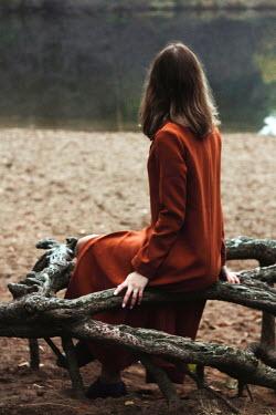 Alina Zhidovinova BRUNETTE WOMAN SITTING ON TREE BRANCH Women