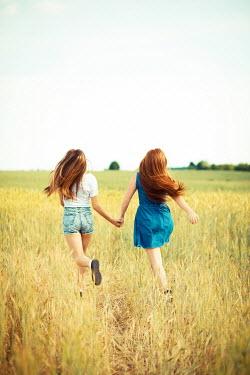 Ildiko Neer Two teenage girls running in wheat field Groups/Crowds