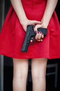 Nina Masic YOUNG WOMAN IN RED DRESS HOLDING GUN Women