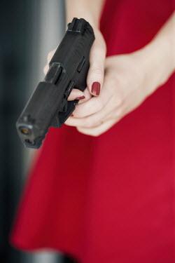 Nina Masic YOUNG WOMAN IN RED DRESS AIMING GUN Women