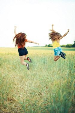 Ildiko Neer Two teenage girls jumping in wheat field Groups/Crowds