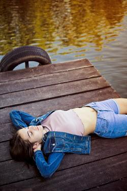 Ildiko Neer Young modern woman lying on lakeside jetty Women