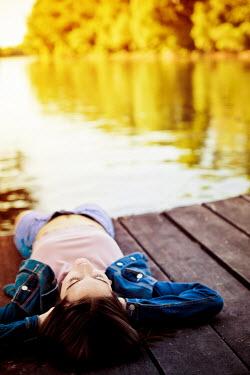 Ildiko Neer Young modern woman laying beside lake Women