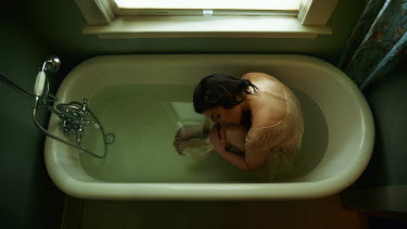 Kate Woodman YOUNG WOMAN SITTING IN BATH TUB Women