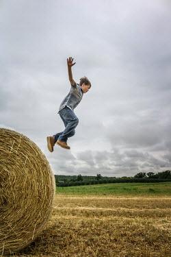 Stephen Carroll BOY JUMPING OFF HAY BALE Children