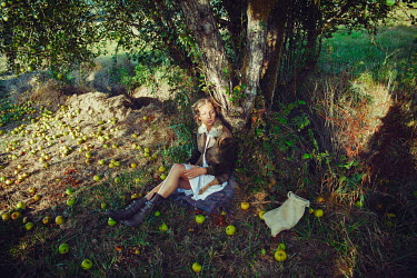 Kate Woodman YOUNG BLONDE WOMAN SITTING IN ORCHARD Women