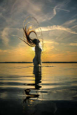 Stephen Carroll WOMAN SPLASHING HAIR IN SEA AT SUNSET Women