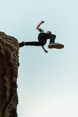 Clayton Bastiani MAN JUMPING OFF ROCK Men