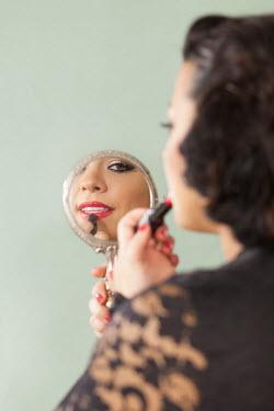 Eva Ricci WOMAN APPLYING LIPSTICK IN MIRROR Women