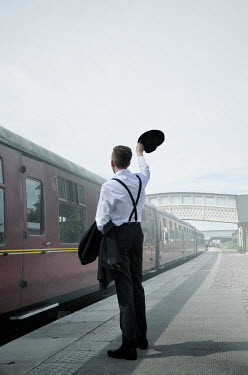 Maggie Brodie RETRO MAN WAVING HAT ON TRAIN PLATFORM Men