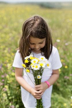 Aida Redzepagic LITTLE BRUNETTE GIRL HOLDING DAISIES IN FIELD Children