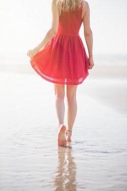 Laura Ranftler WOMAN IN RED DRESS WALKING ON SANDY BEACH Women