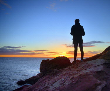 Maggie Brodie MAN ON ROCK WATCHING SUNSET AT SEA Men