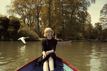 Marta Bevacqua WOMAN IN BOAT ON LAKE WITH FLYING SWAN Women