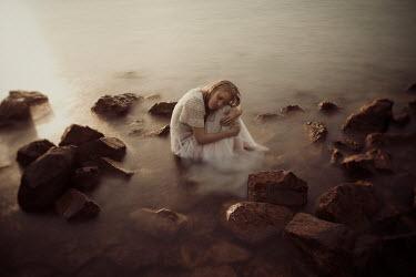 Eva Van Oosten VINTAGE WOMAN SITTING BY ROCKS IN SEA Women
