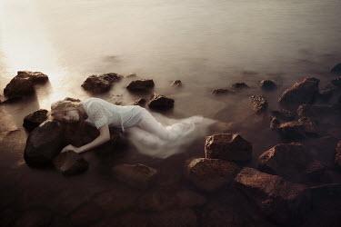 Eva Van Oosten SHIPWRECKED WOMAN LYING ON ROCKS BY SEA Women