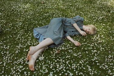 Marta Bevacqua YOUNG BLONDE WOMAN LYING IN DAISY FIELD Women